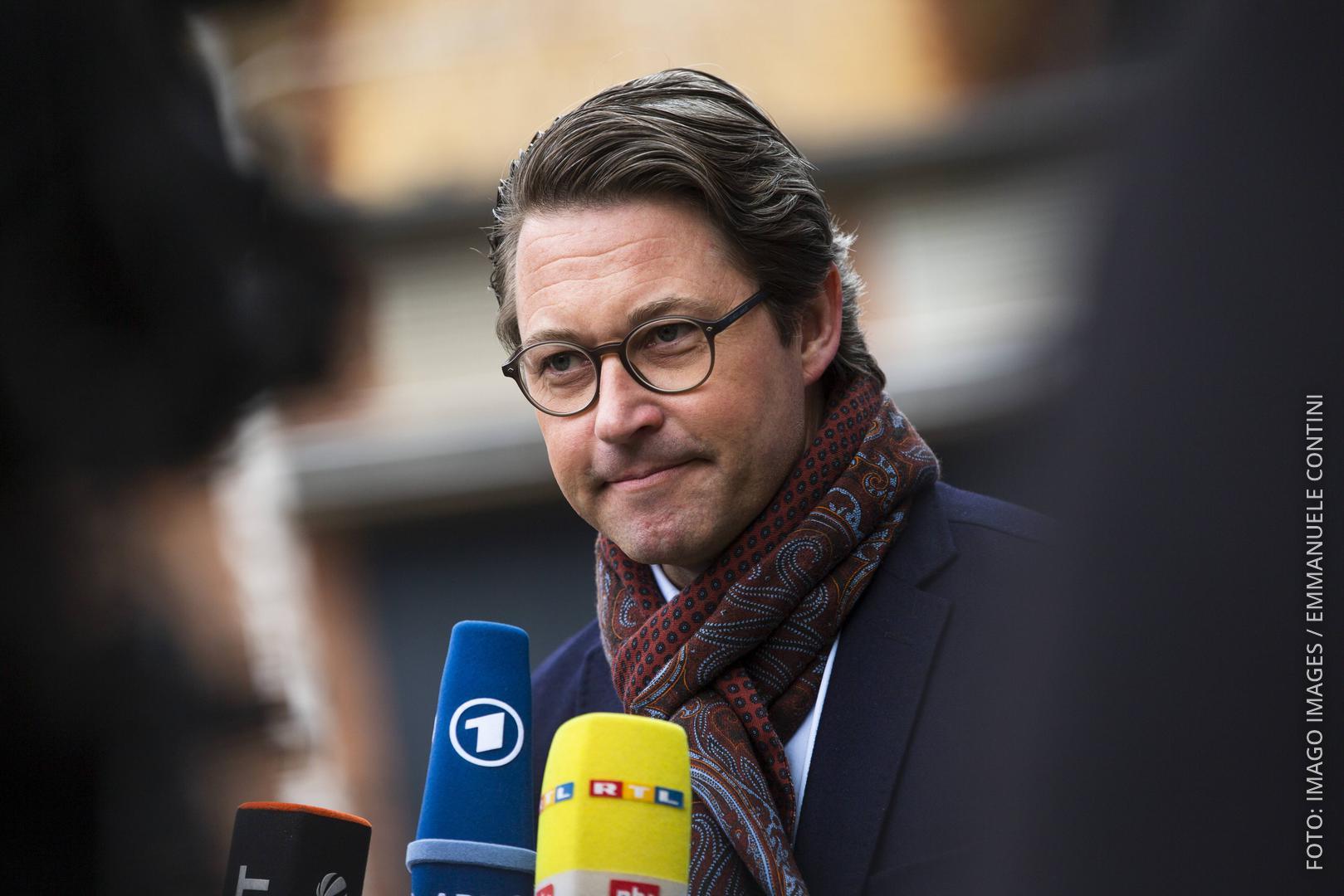 Bundesverkehrsminister Scheuer vor zwei Mikrofonen von RTL und ARD.