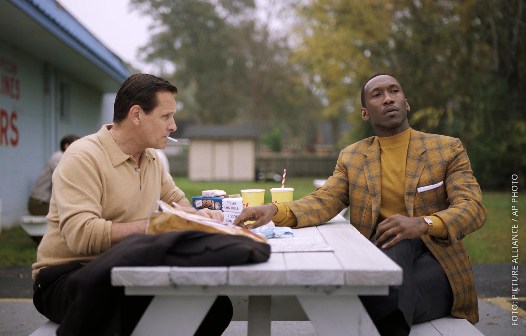 Szene aus dem Film Green Book. Beide Hauptdarsteller sitzen an einem Tisch