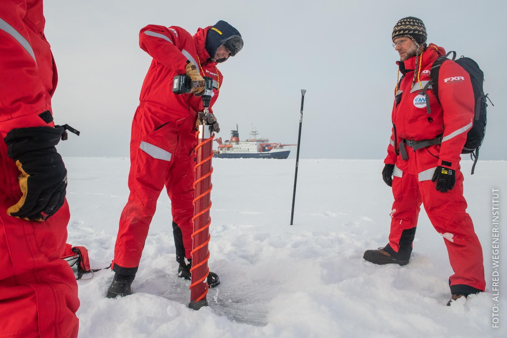 Forscher stehen auf Eisscholle und bohren hinein