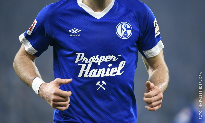 """Schalke-Spieler Daniel Caligiuri trägt ein Trikot mit der Aufschrift """"Prosper Haniel""""."""