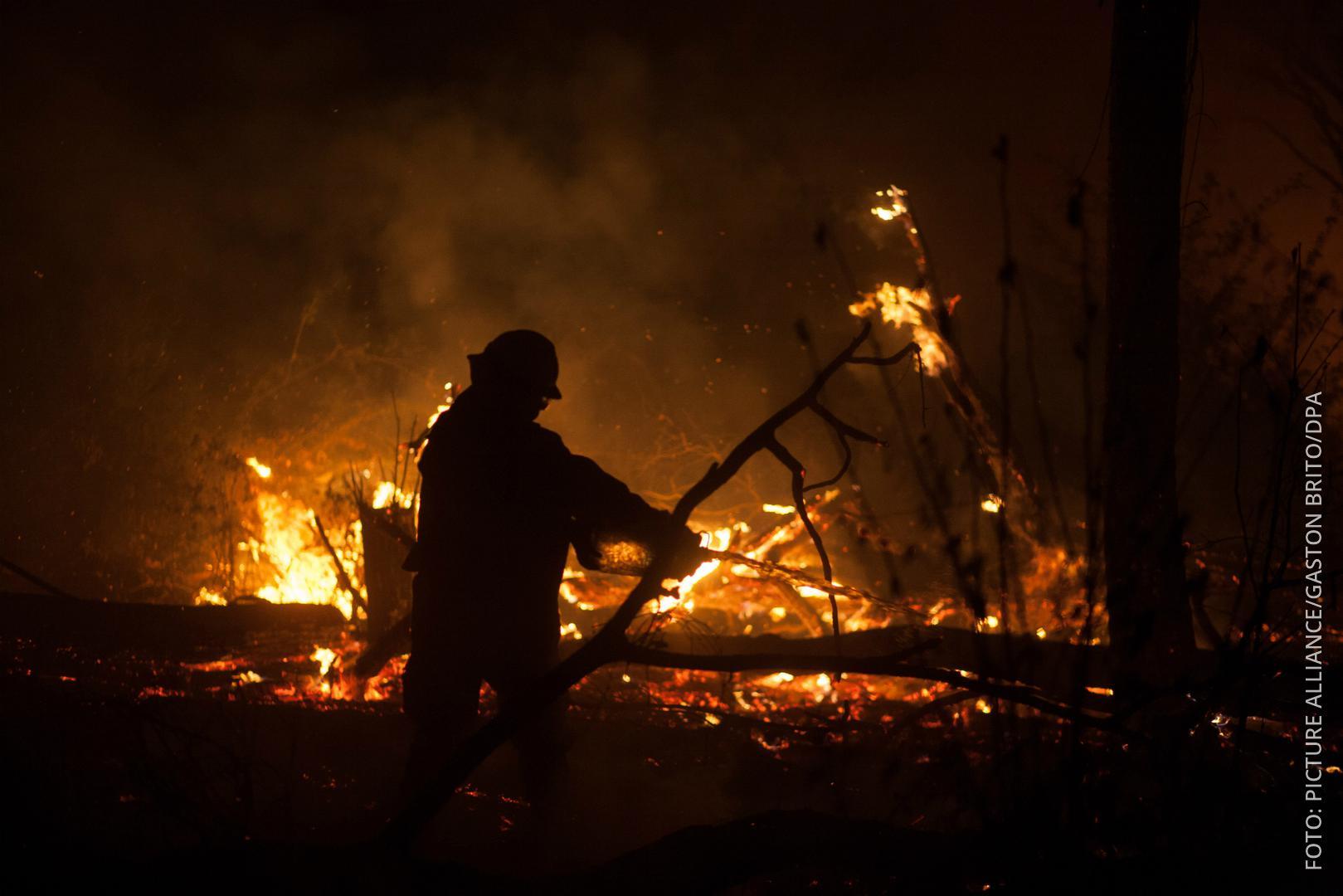 Ein Feuerwehrmann steht vor einem brennenden Wald in Bolivien.