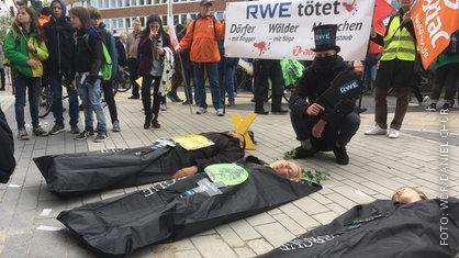 Klimaschützer liegen als Baum in schwarze Leichensäcke gehüllt