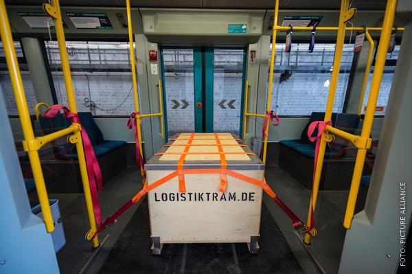 Ein Paketwagen ist mit Gurten in der Straßbahn befestigt