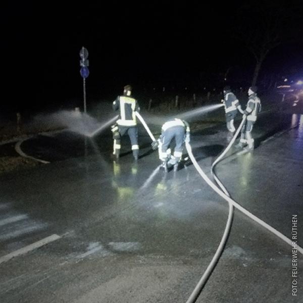 Die Freiwillige Feuerwehr versucht mit Wasserschläuchen die Milch von der Straße zu kriegen.