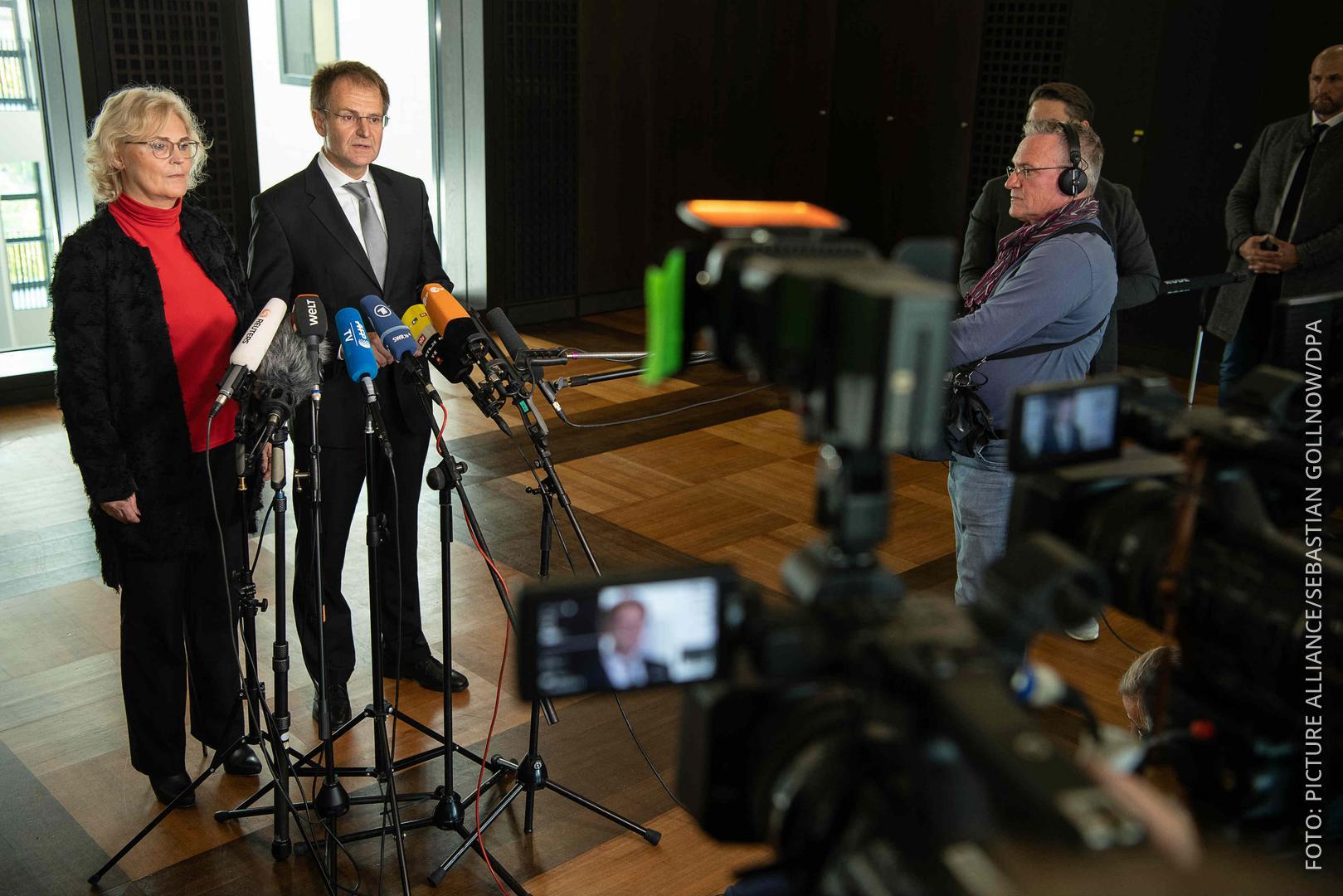 Der Generalbundesanwalt steht zusammen mit der Justizministerin vor Fernsehkameras.