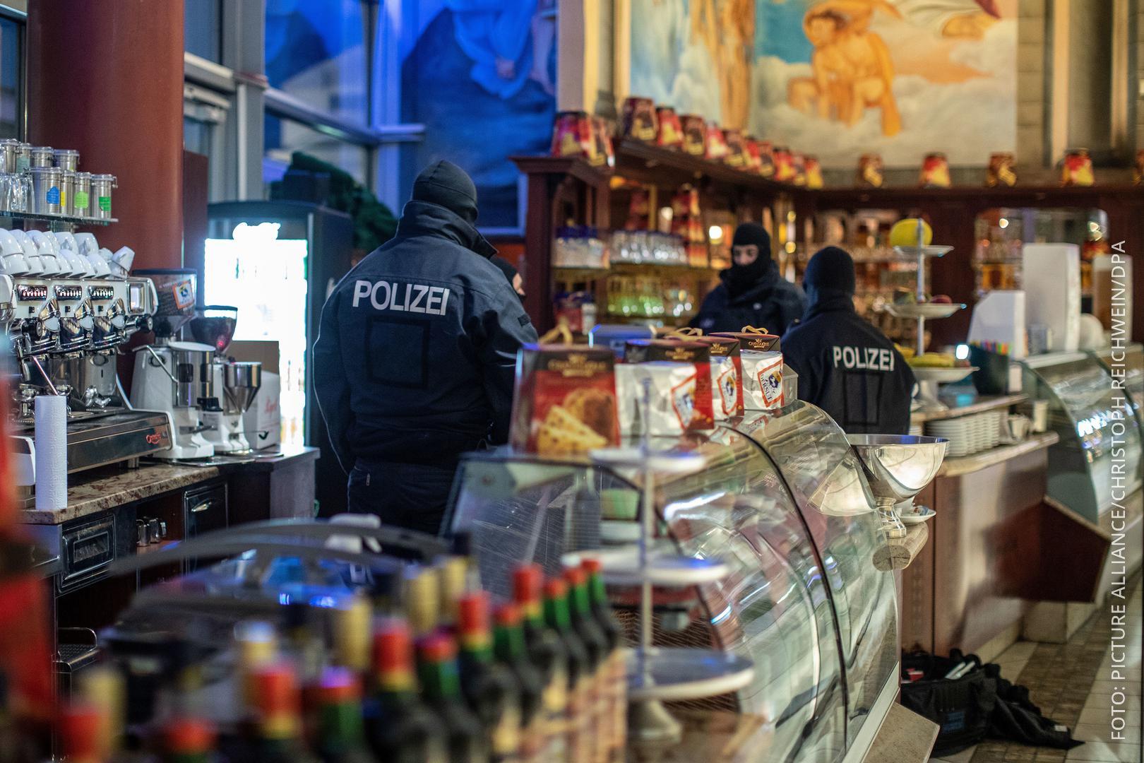 Polizisten stehen in einem Eiscafé im Citypalais in der Duisburger Innenstadt.