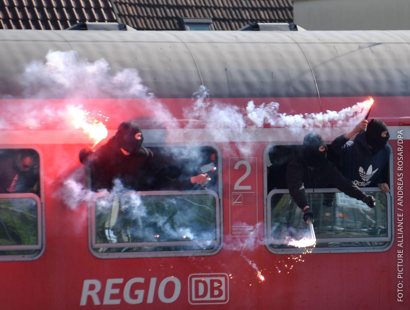 Vermummte Fußballfans schauen aus einem Regionalzug udn zündne Bengalos