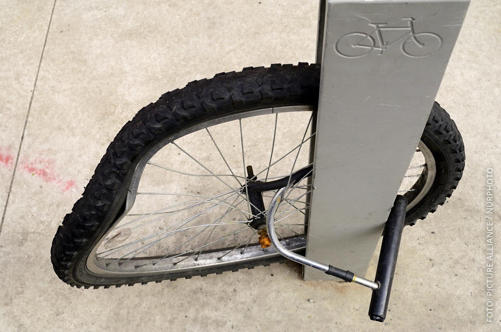 Ein einzelnes Rad von einem Fahrrad hängt an einem Fahrradschloss.