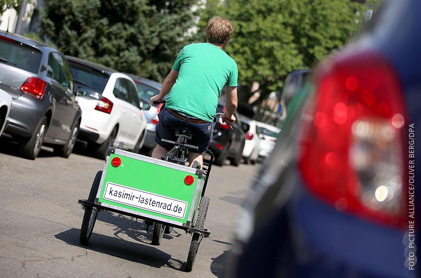Radfahrer unterwegs mit einem Lastenrad