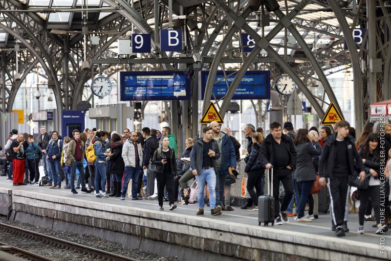 Pendler warten am Kölner Hauptbahnhof auf ihrem Zug