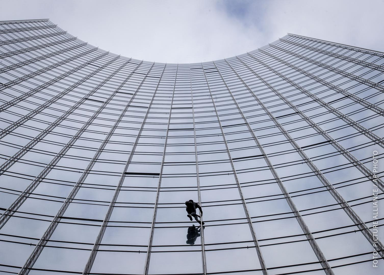 Der Kletterer Alain Robert hängt an der Fassade des Hochhauses in Frankfurt