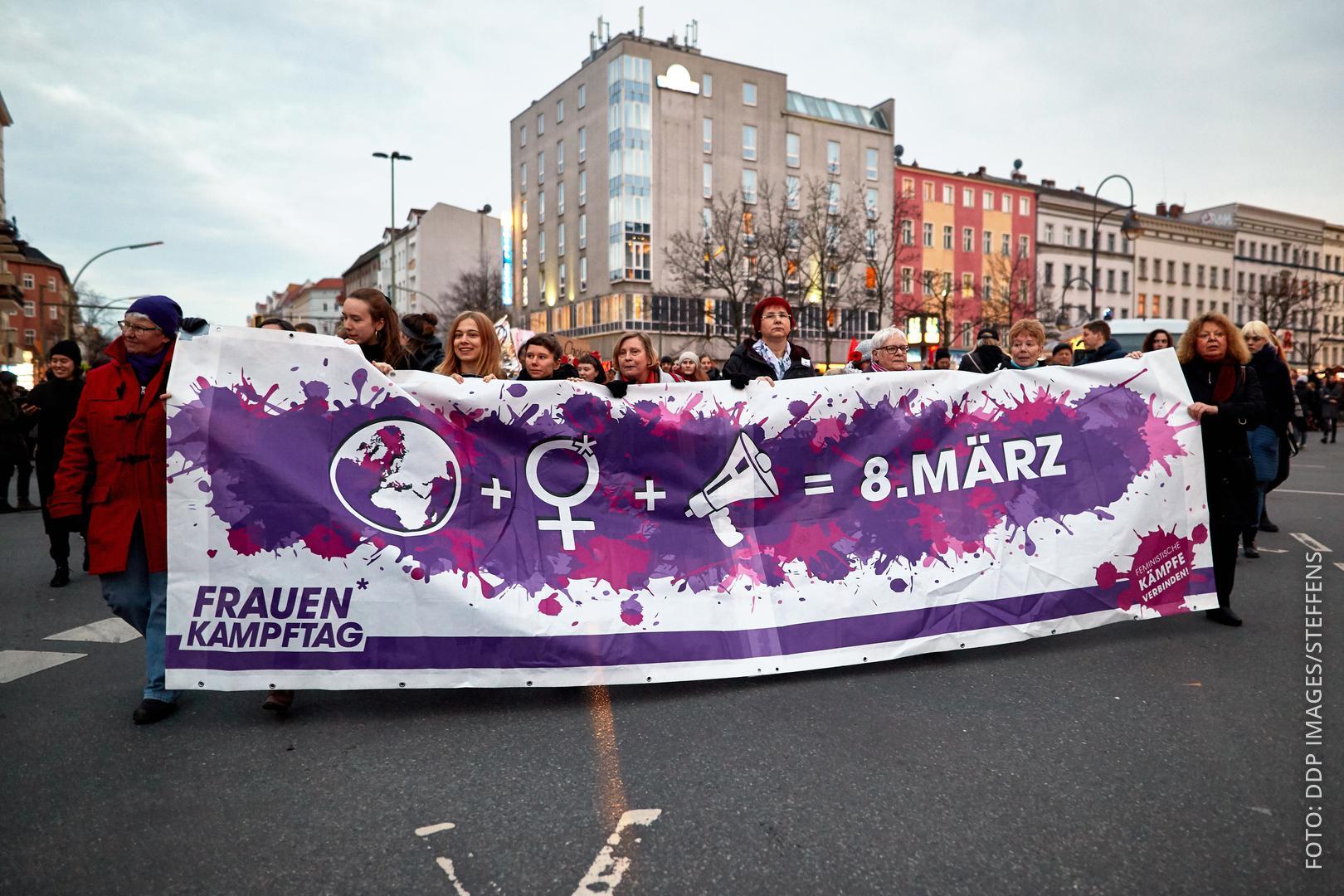 """Frauen demonstrieren für mehr Rechte. Sie halten ein Transparent mit der Aufschrift """"8. März - Weltfrauentag""""."""