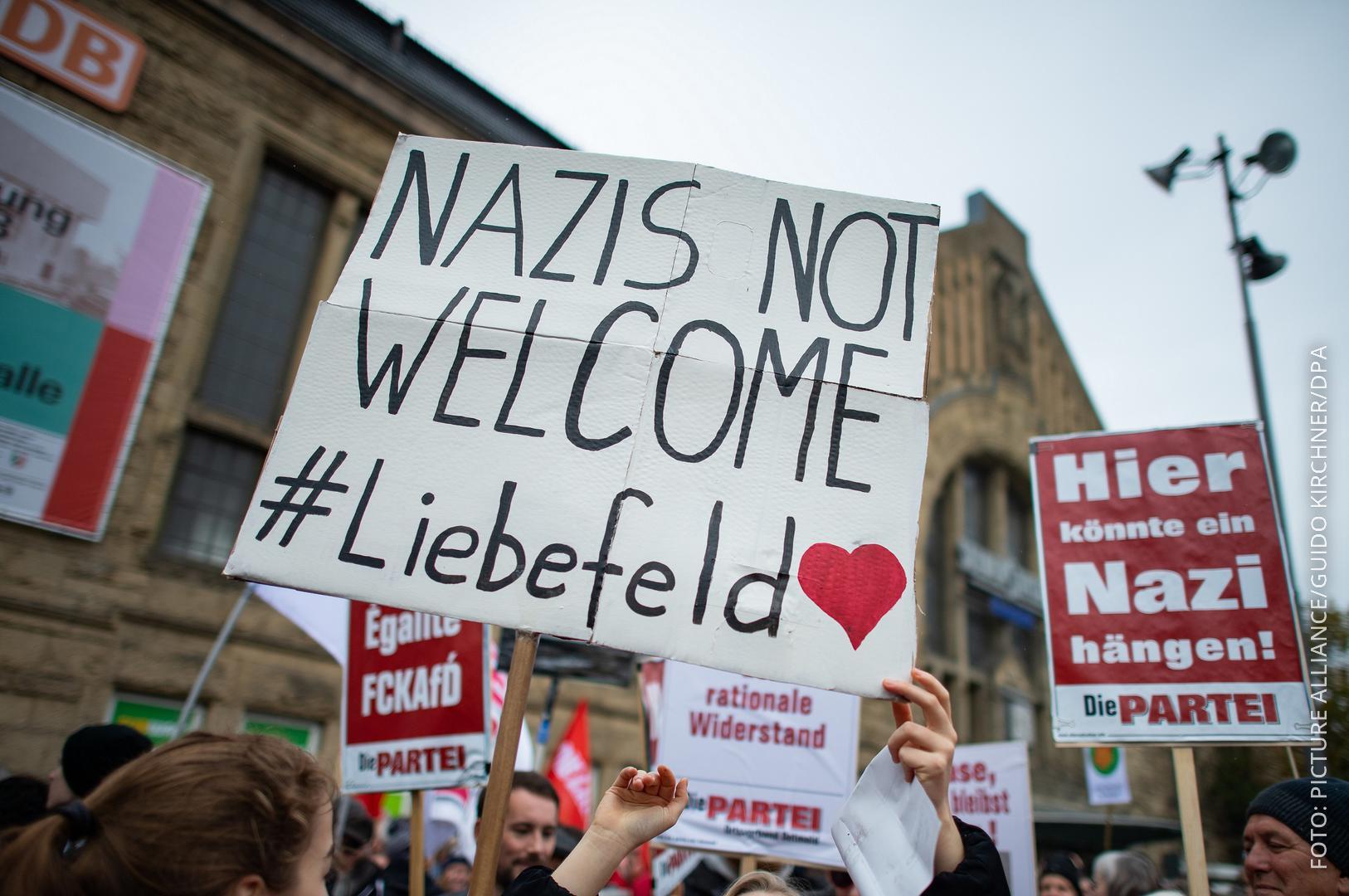 Menschen halten ein Schild mit Spruch gegen Nazis hoch