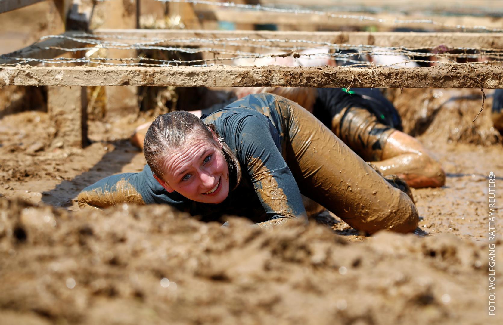 Eine Frau kriecht durch den Schlamm beim Tough-Mudder-Lauf.