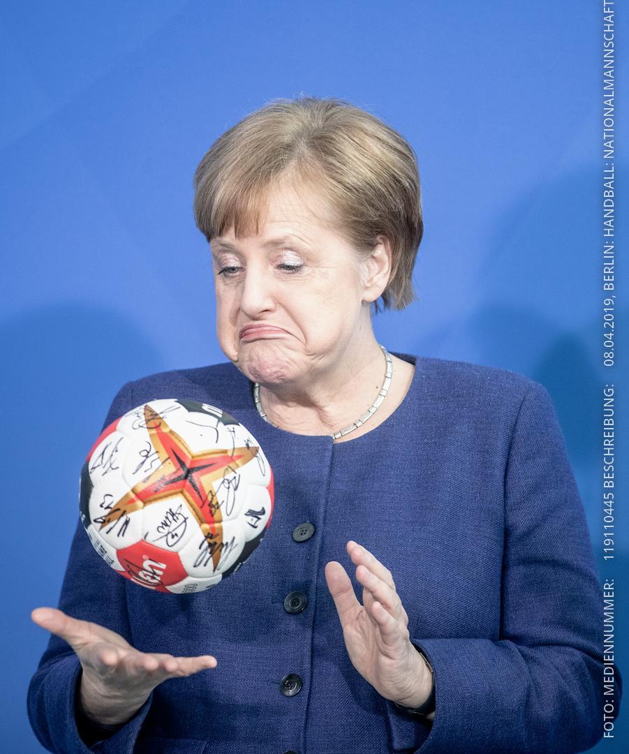 Merkel schaut auf signierten Handball