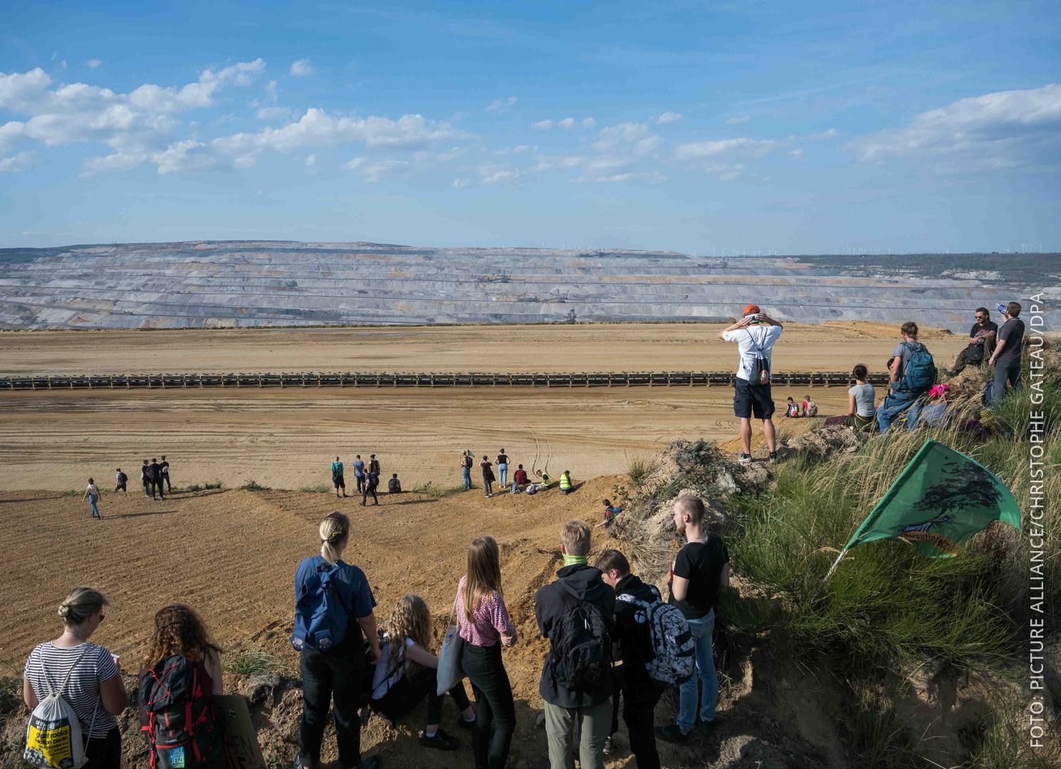Demo-Teilnehmer stehen an der Abrisskante des Hambacher Tagebaus
