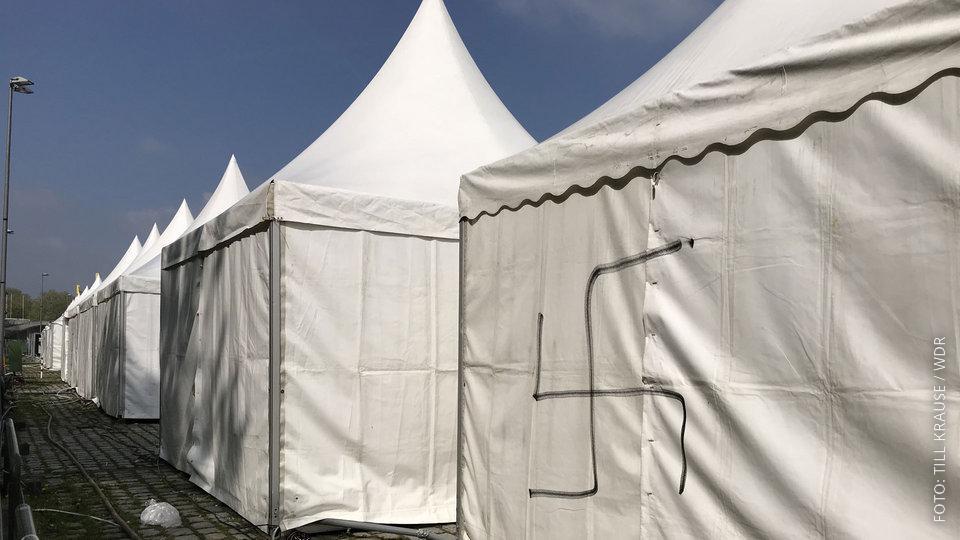 weiße Zelte haben eine Hakenkreuz aufgesprayt