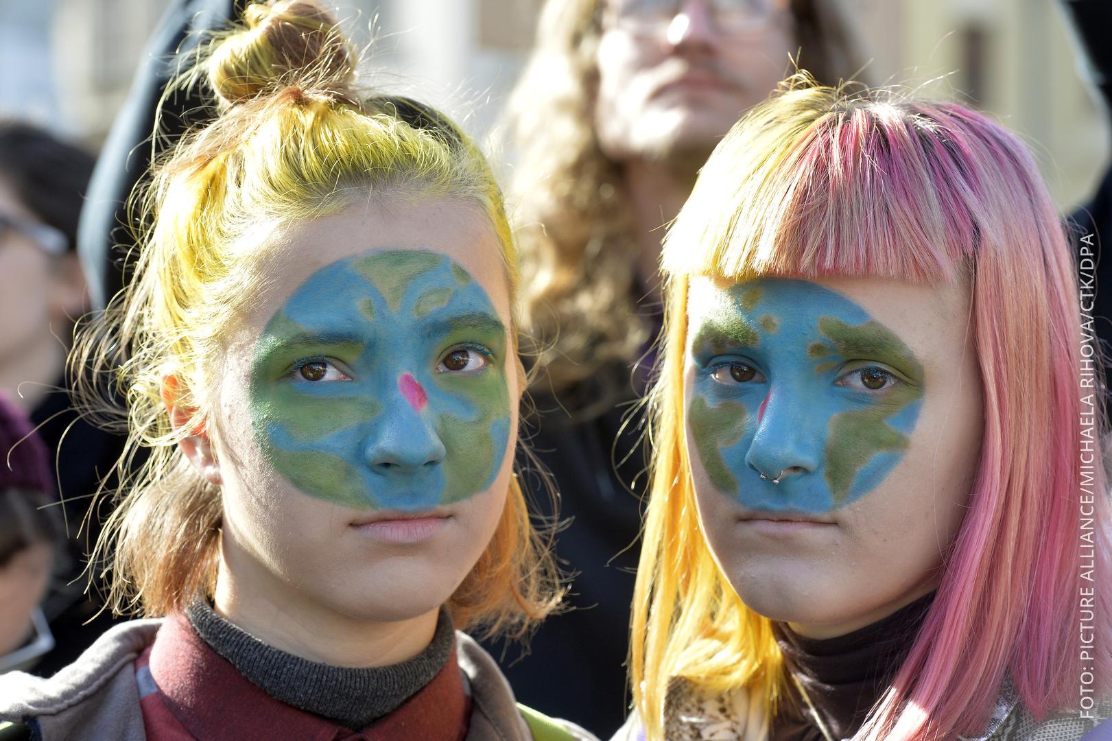 Zwei Mädchen nebeneinander, sie haben auf dem Gesicht eine Erde geschminkt
