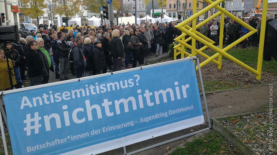 Hunderte Menschen stehen auf einem Platz in Dortmund und erinnern mit Bannern an die Opfer der Pogromnacht