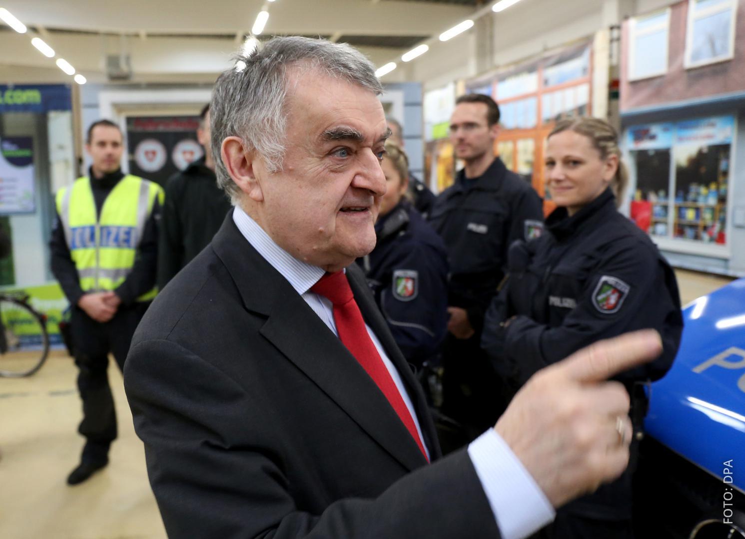 NRW-Innenminister Herbert Reul mit Polizisten im Hintergrund.