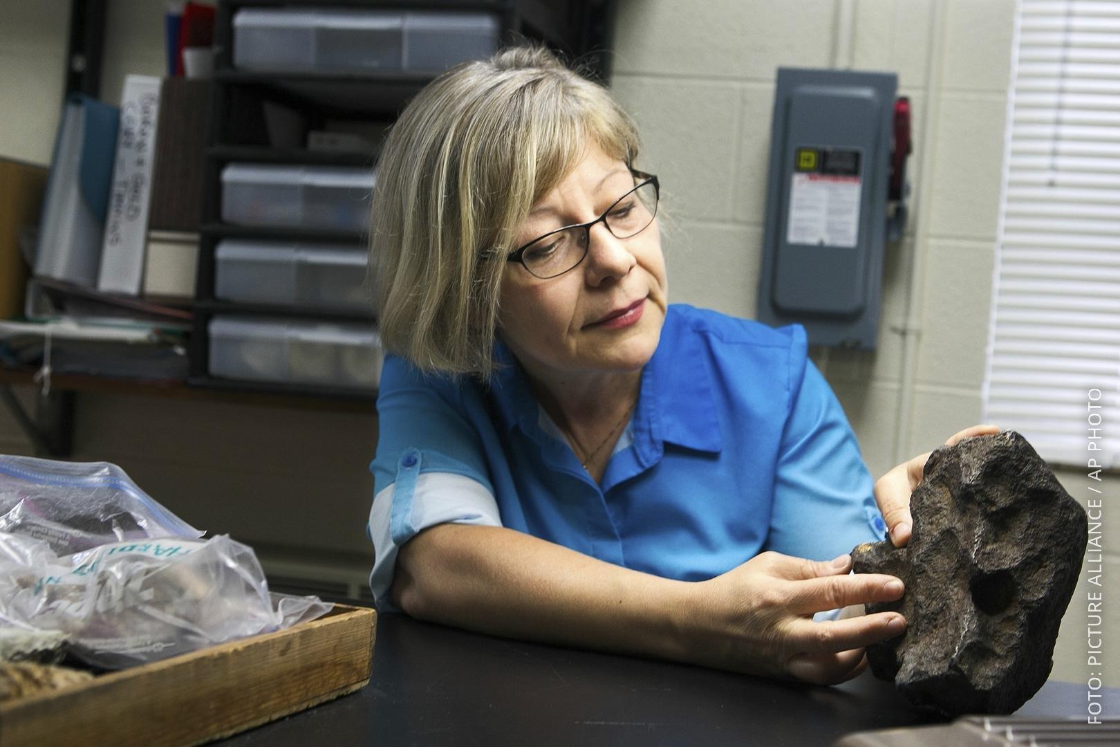 Eine Geologieprofessorin untersucht den gefundenen Meteoriten