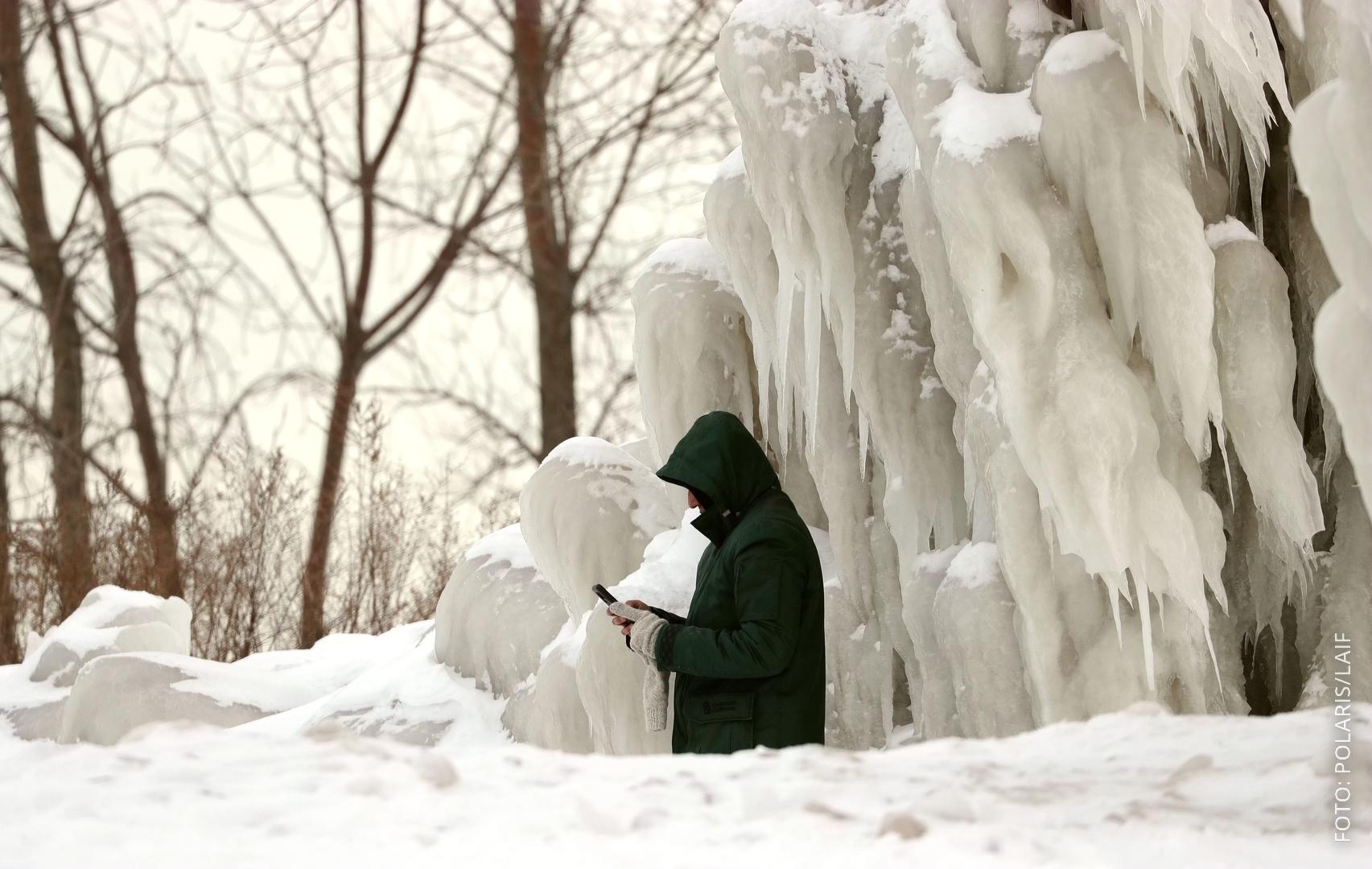 Ein Mann steht mit seinem Smartphone vor riesigen Säulen aus Eis.