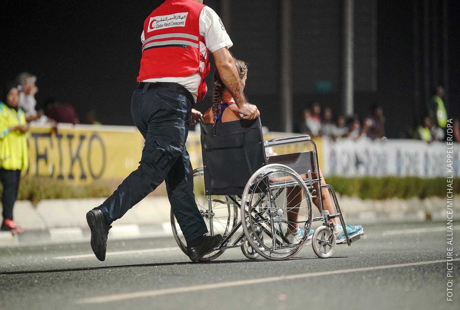 Athletin wird im Rollstuhl von der Strecke geschoben