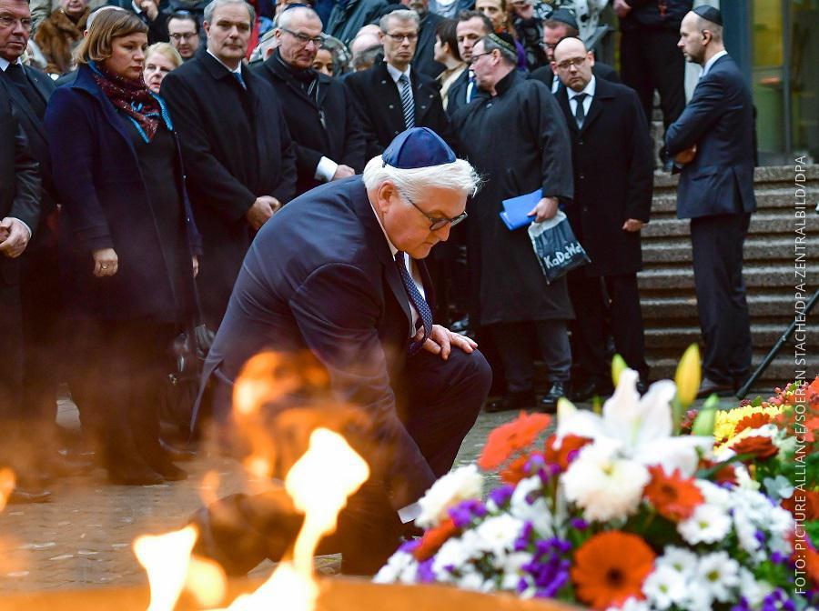 Bundespräsident Steinmeier kniet mit einer Kippa auf dem Boden und zündet eine Kerze an