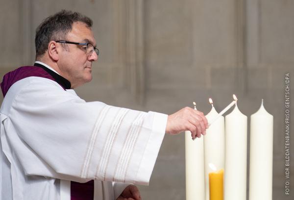 Der Pfarrer in Münster zündet vier Kerzen für die Opfer der Amokfahrt an