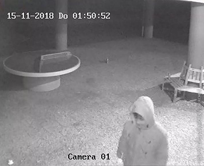 Ein Foto einer Überwachungskamera zeigt eine Person mit heller Jacke, einer Kapuze überm Kopf und einem Tuch vorm Mund.