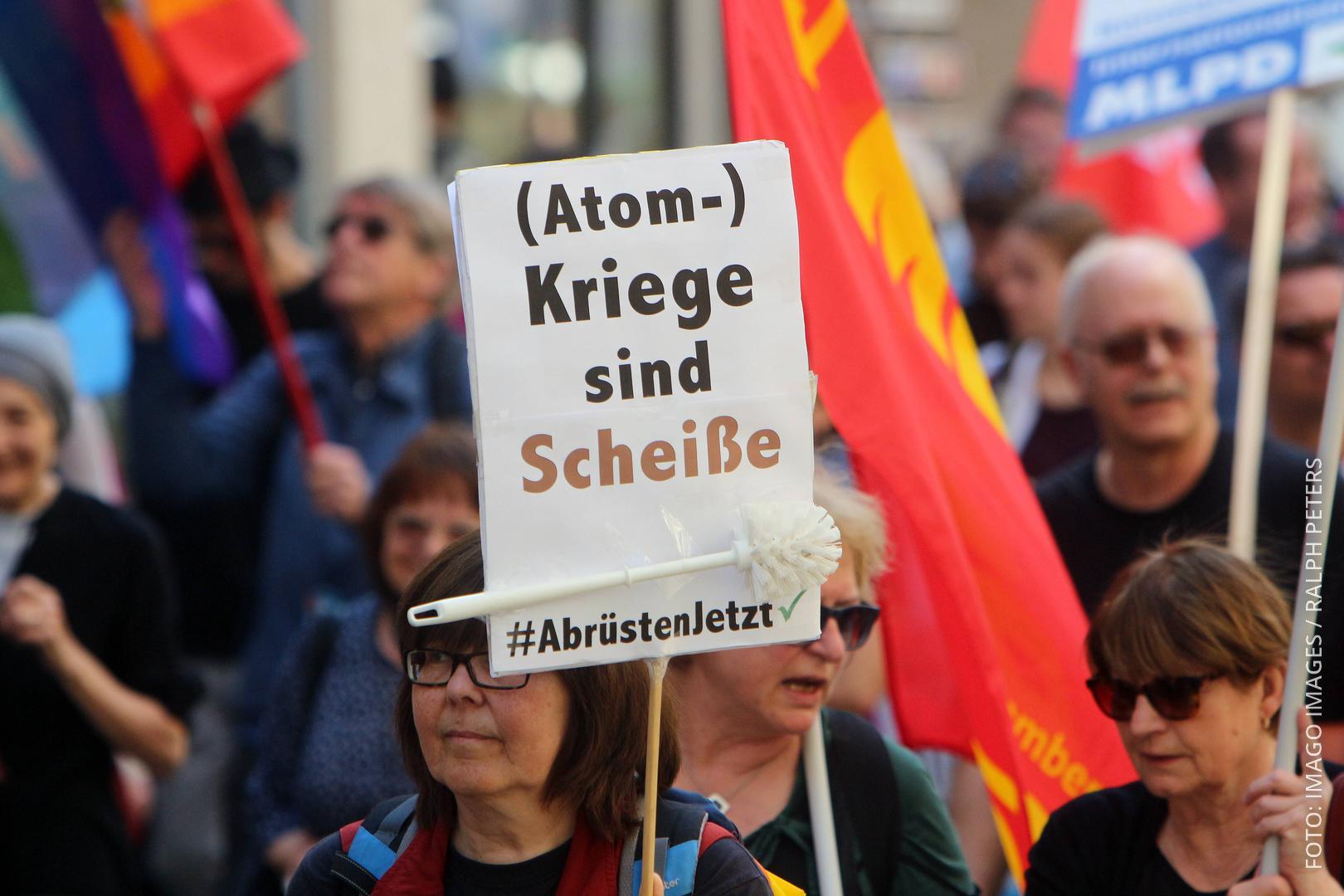 """Eine Demonstrantin hält ein Plakat hoch, auf dem steht: """"Atom-Kriege sind Scheiße""""."""