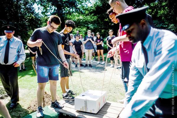 Vier Schüler lassen den Karton mit dem Skelett in das Grab auf dem Nordfriedhof in Dortmund ein.
