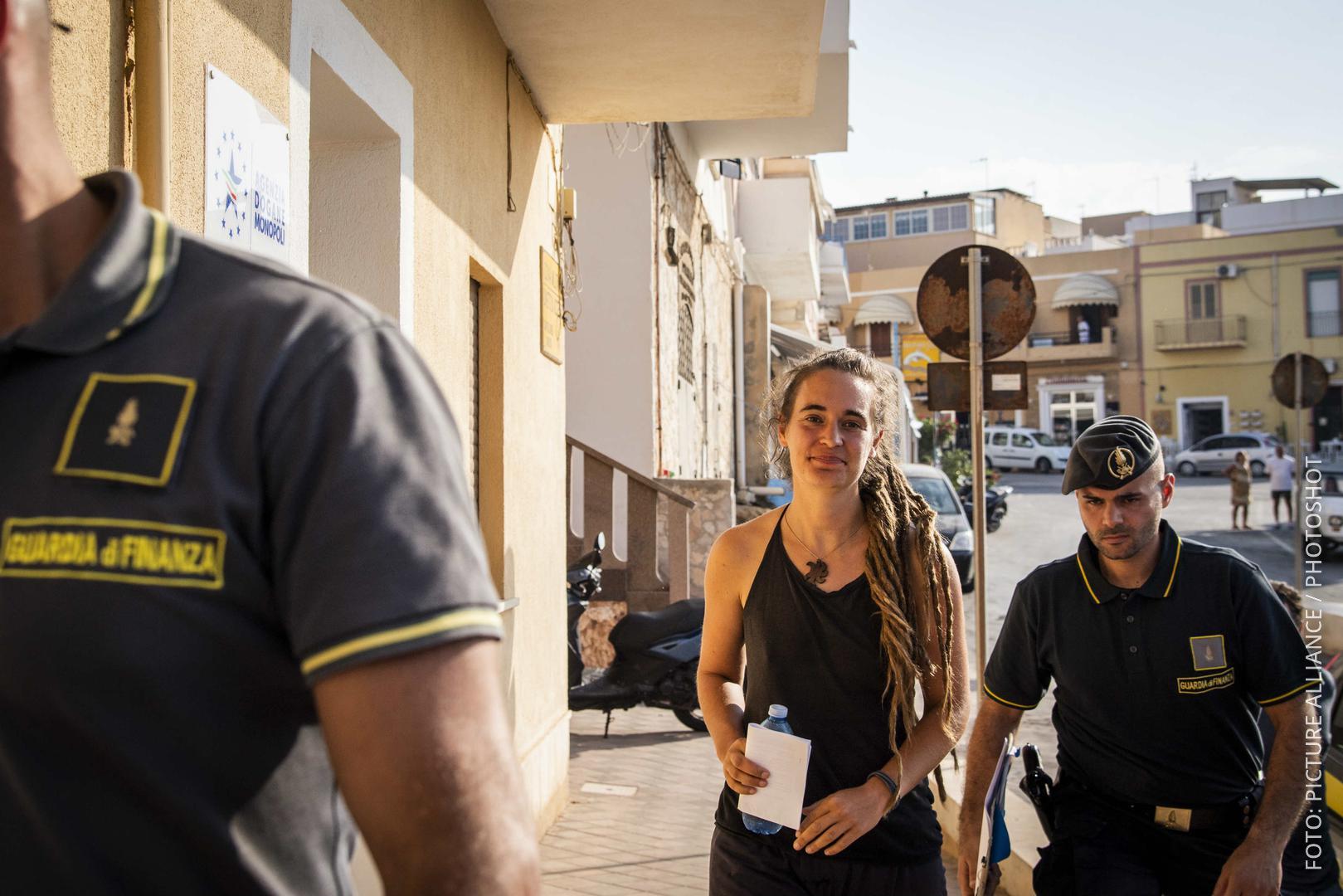 Carola Rackete wird von Polizisten abgeführt.