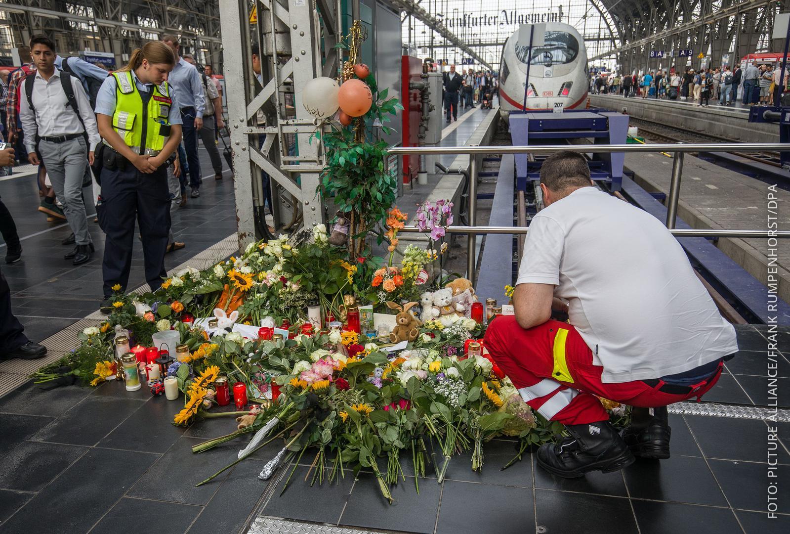 Menschen legen Blumen und Stofftiere am Frankfurter Bahnhof nieder.