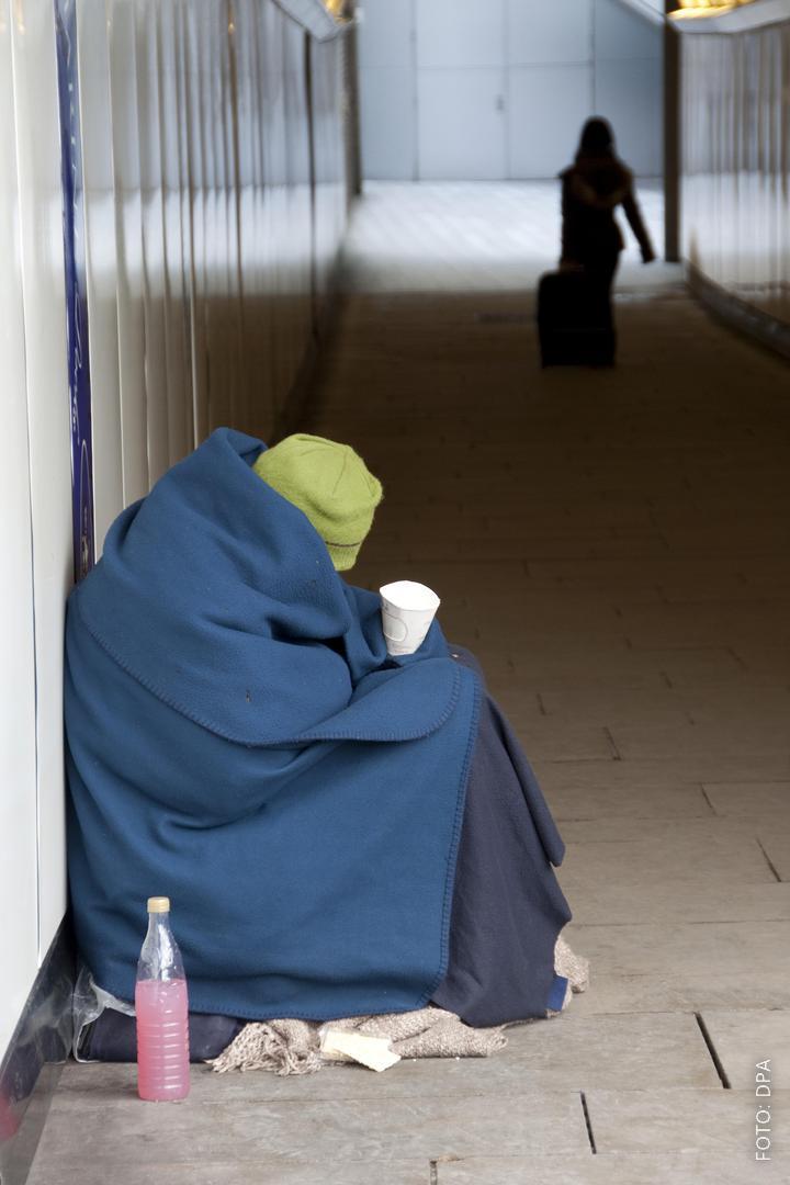 Obdachlose sitzt auf Straße