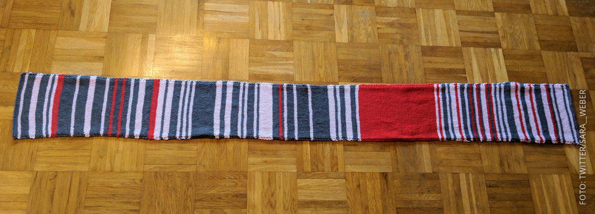 Ein bunter Schal in den Farben rot, weiß, grau und rosa