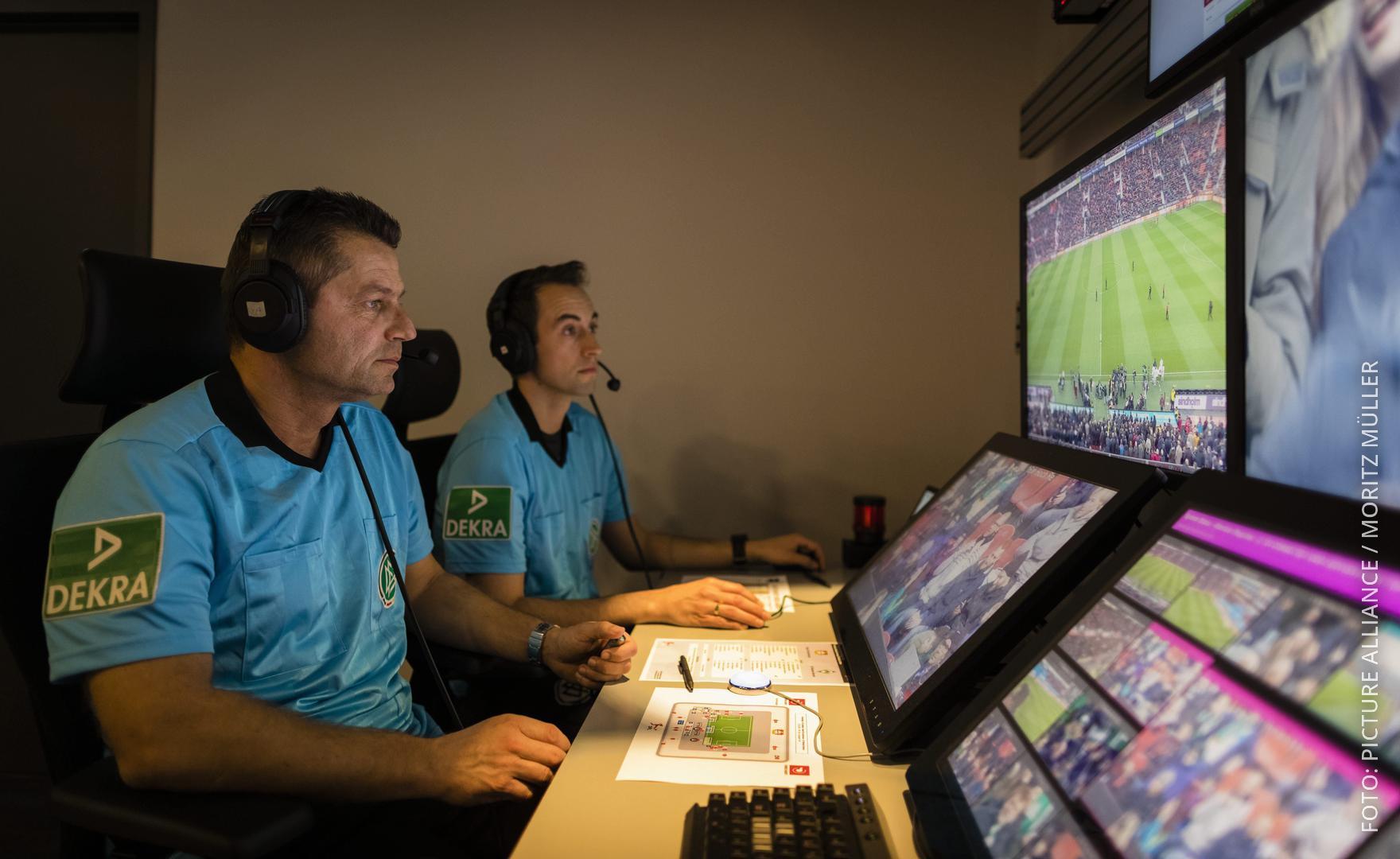 Zwei Videoschiedsrichter schauen auf den Bildschirm und prüfen die Aktion