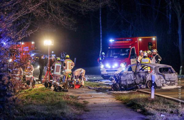 Ausgebranntes Autowrack / Feuerwehrleute im Einsatz