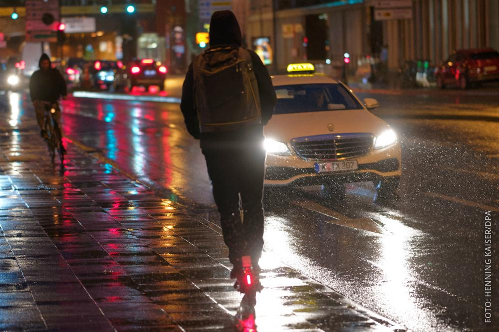Ein E-Scooter-Fahrer fährt im Dunkeln bei Regen.