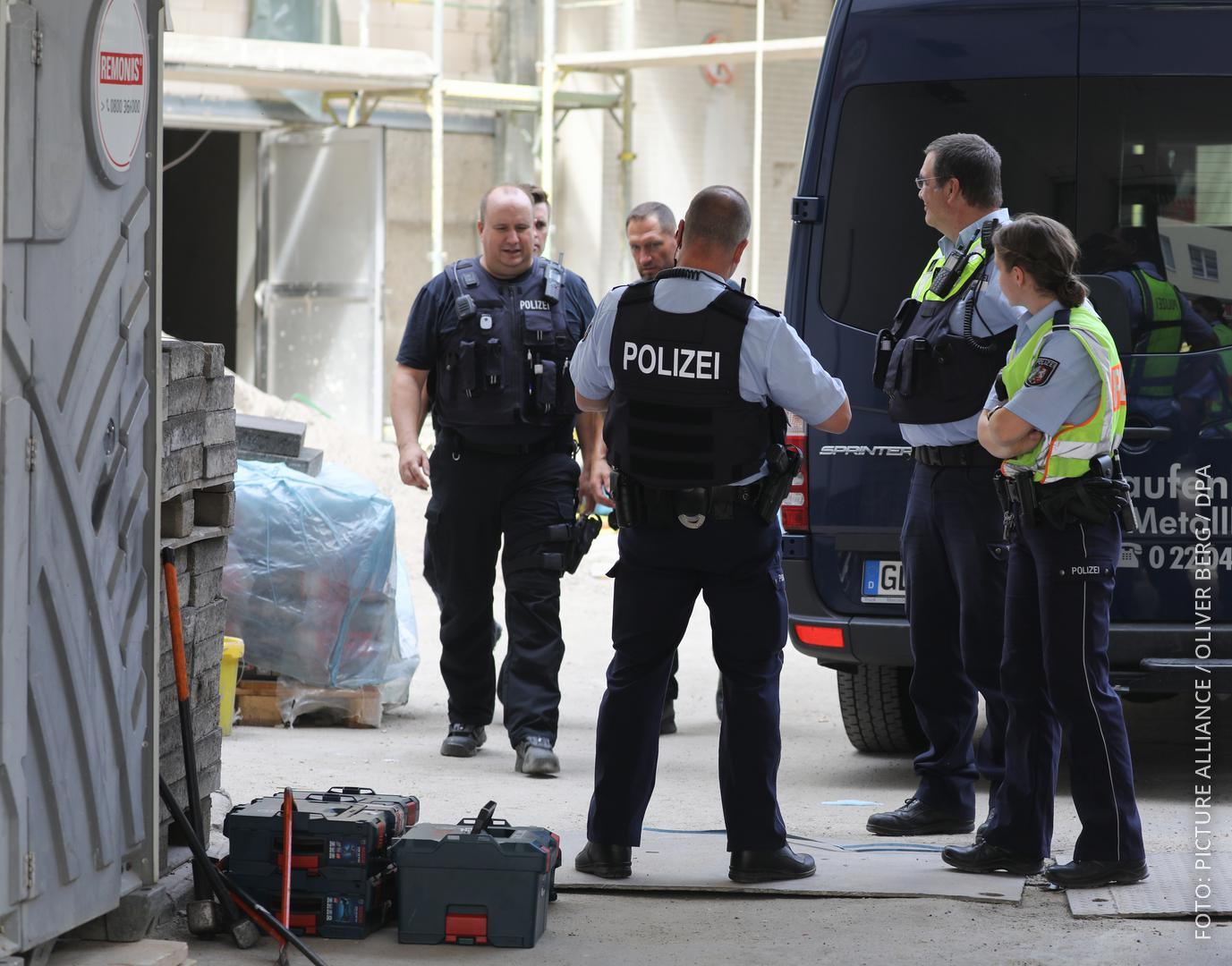 Köln: Polizisten stehen vor dem Hintereingang eines Wohngebäudes in der Innenstadt.