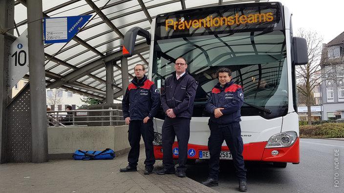 Drei Männer stehen vor einem Bus