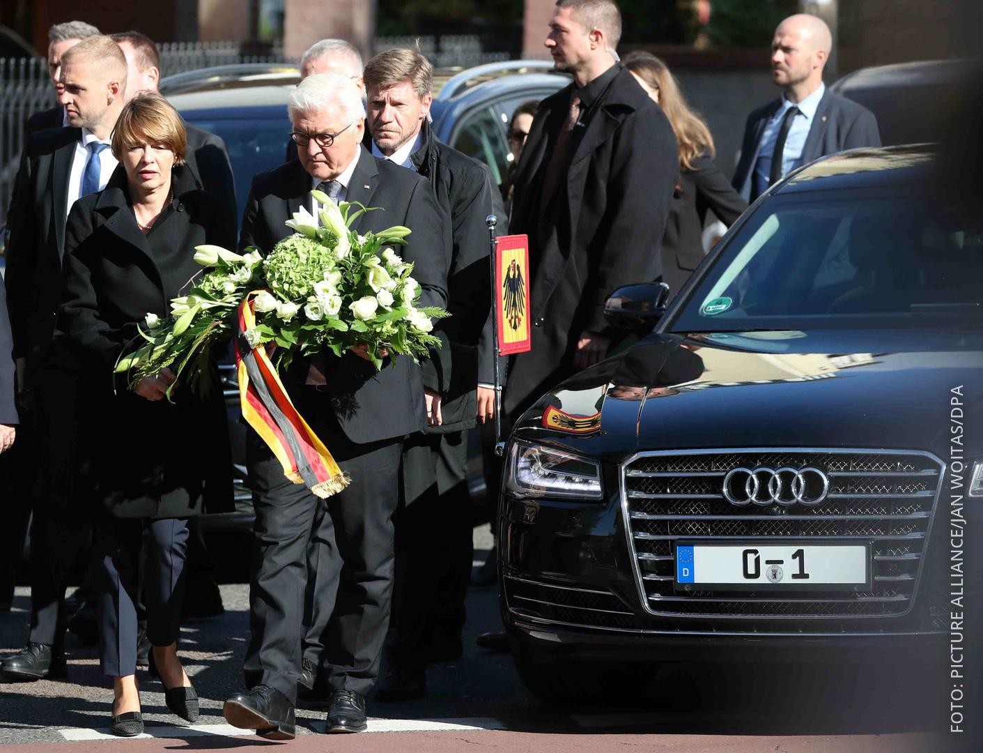 Bundespräsident Steinmeier trägt einen Kranz.