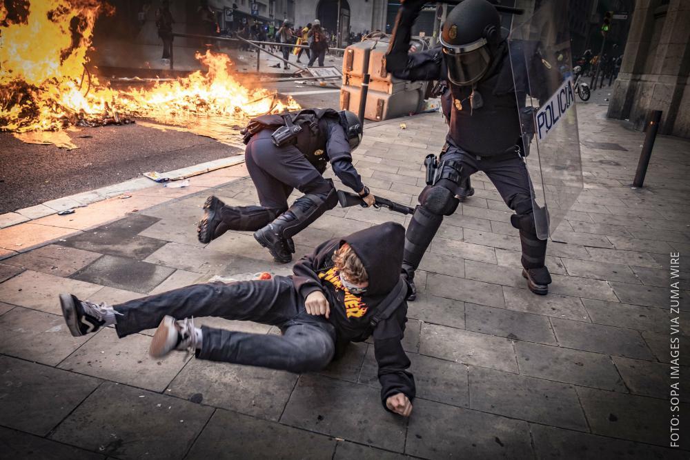 Ein Polizist schlägt einen Demonstranten in Barcelona