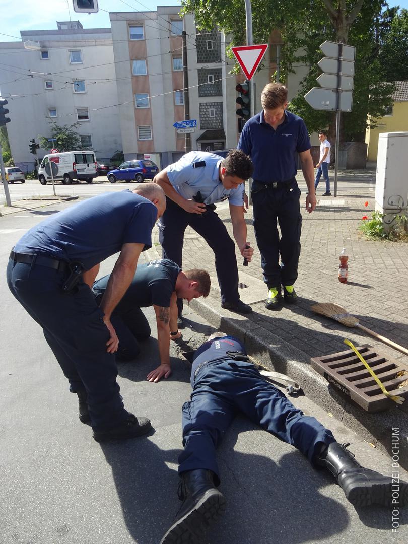 Einsatzkräften retten ein Küken aus einem Gully