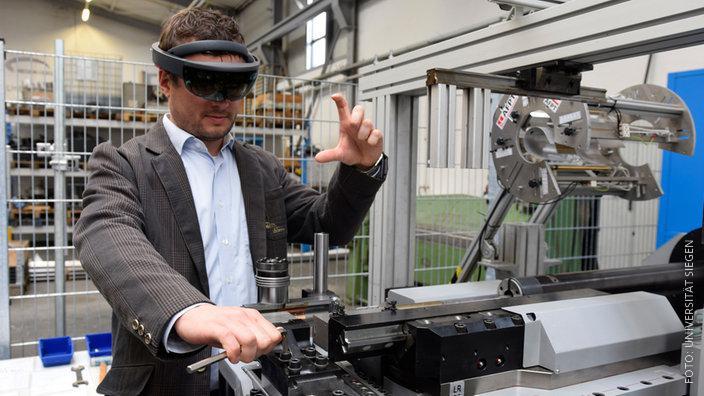 Mitarbeiter steht mit Cyberbrille an einer Maschine