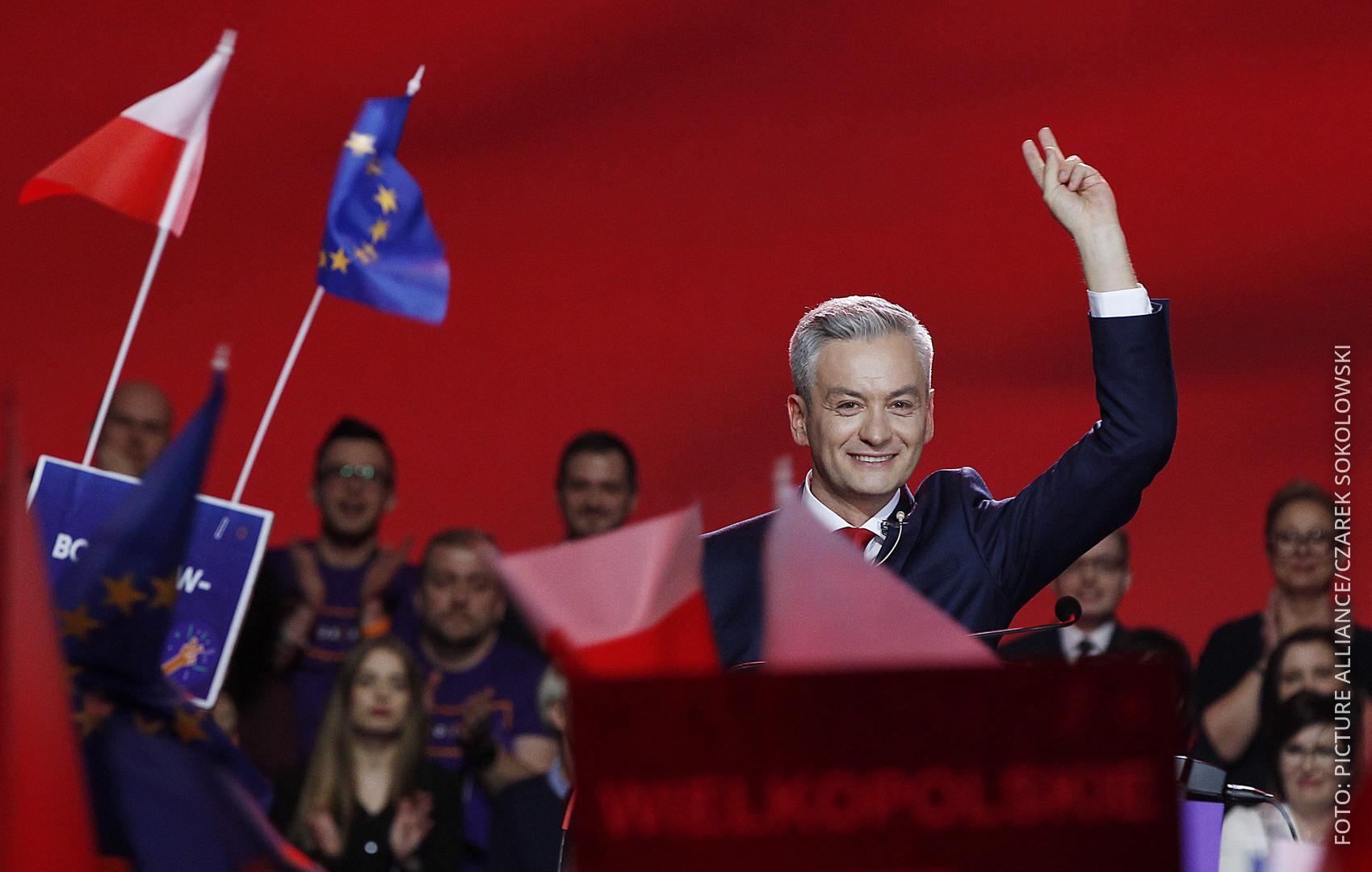 Politiker Robert Biedron steht am Sprecherpult, winkt und freut sich