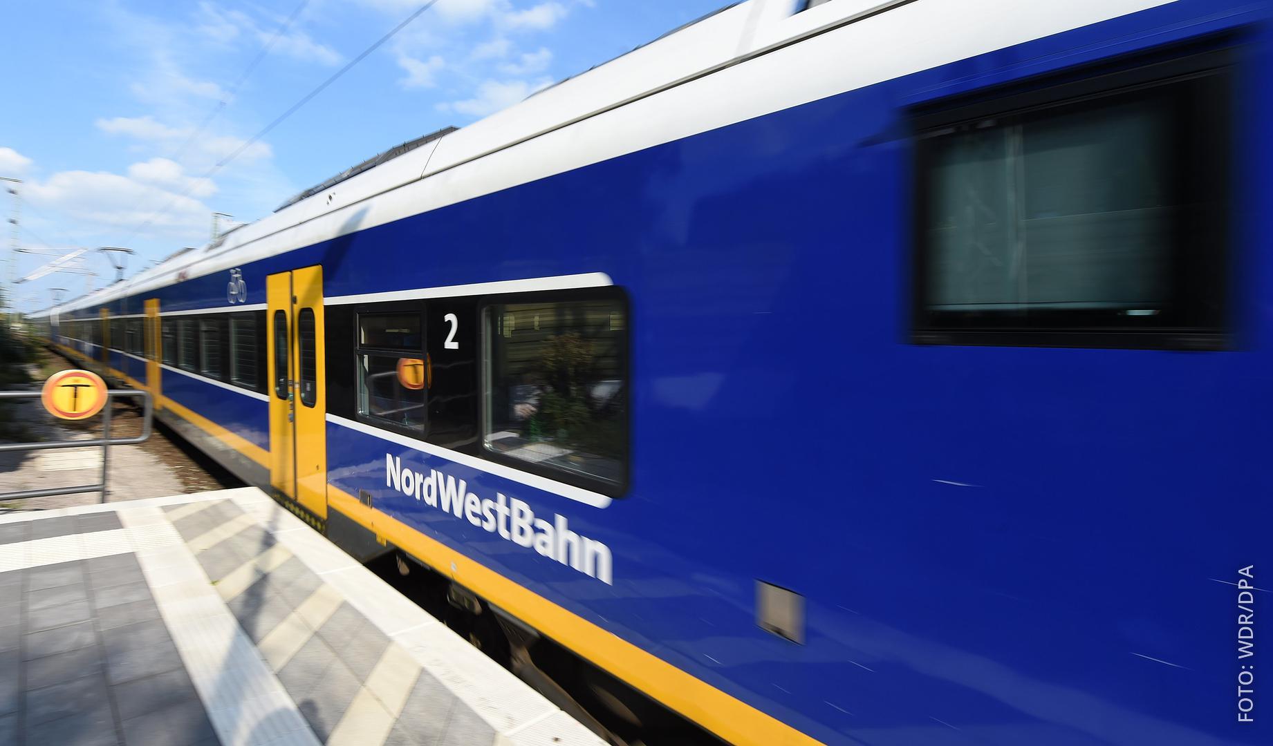 Ein Zug der Nordwestbahn fährt durch einen Bahnhof.