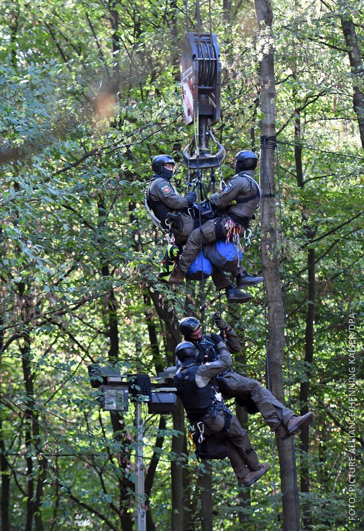 Polizisten seilen sich von einem Kran zu einem Baumhaus im Hambacher Forst ab.