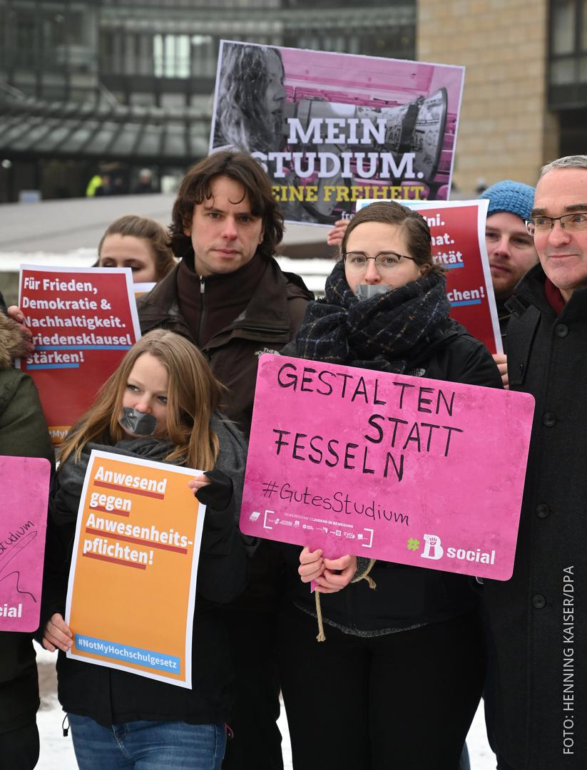 Studenten halten vor dem Landtag Protestplakate hoch.