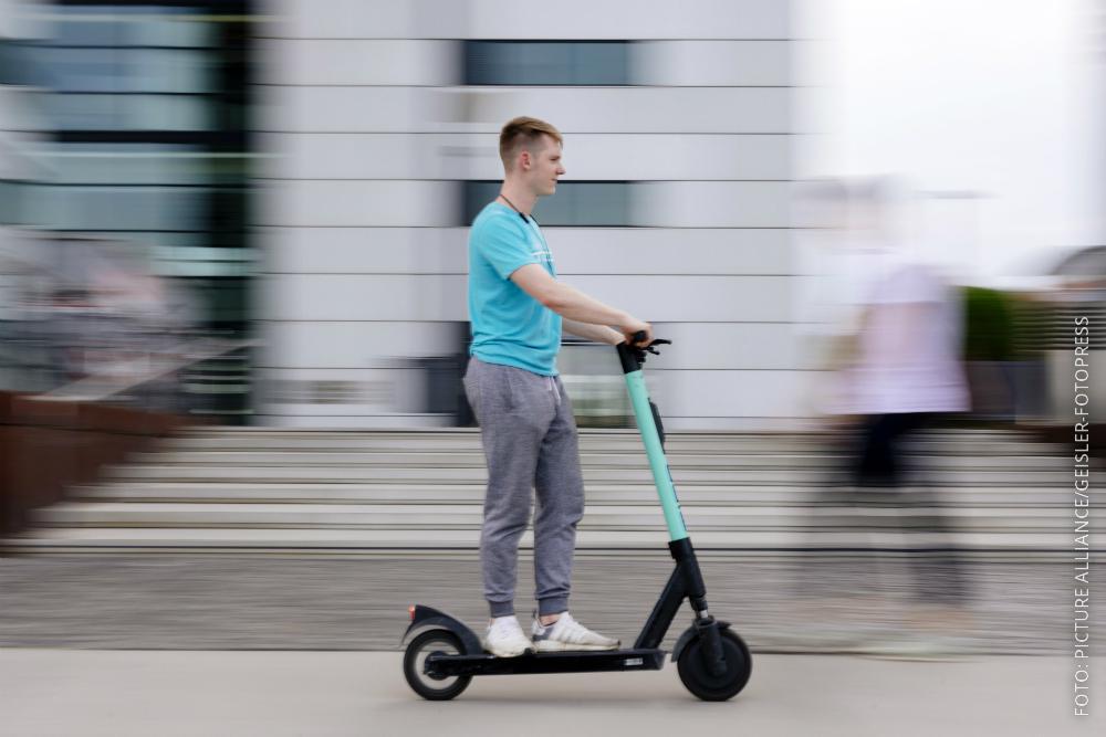 Ein Mann fährt auf einem E-Scooter.